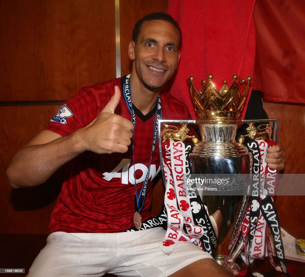 Rio Ferdinand of Manchester United celebrates with the Barclays Premier League trophy in the dressing room after the Barclays Premier League match between Manchester United and Swansea City at Old Trafford on May 12, 2013 in Manchester, England.