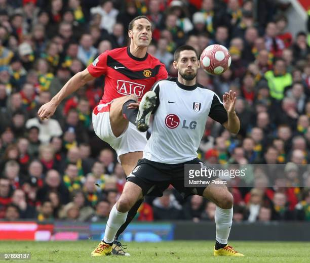 Rio Ferdinand of Manchester United clashes with Clint Dempsey of Fulham during the FA Barclays Premier League match between Manchester United and...