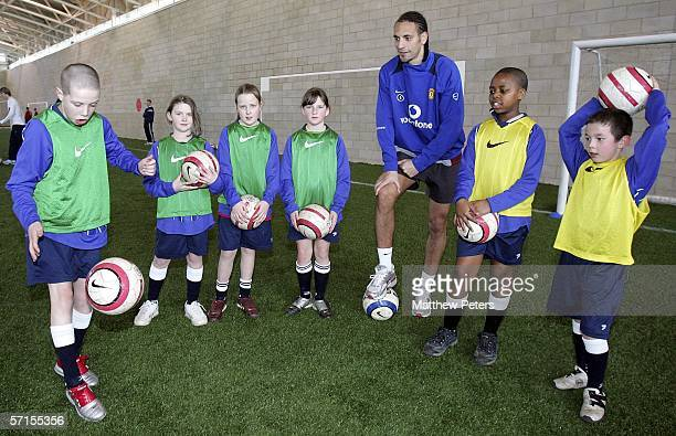 Rio Ferdinand of Manchester United coaches local school children after the press conference to announce the club's plans to celebrate the 50th...