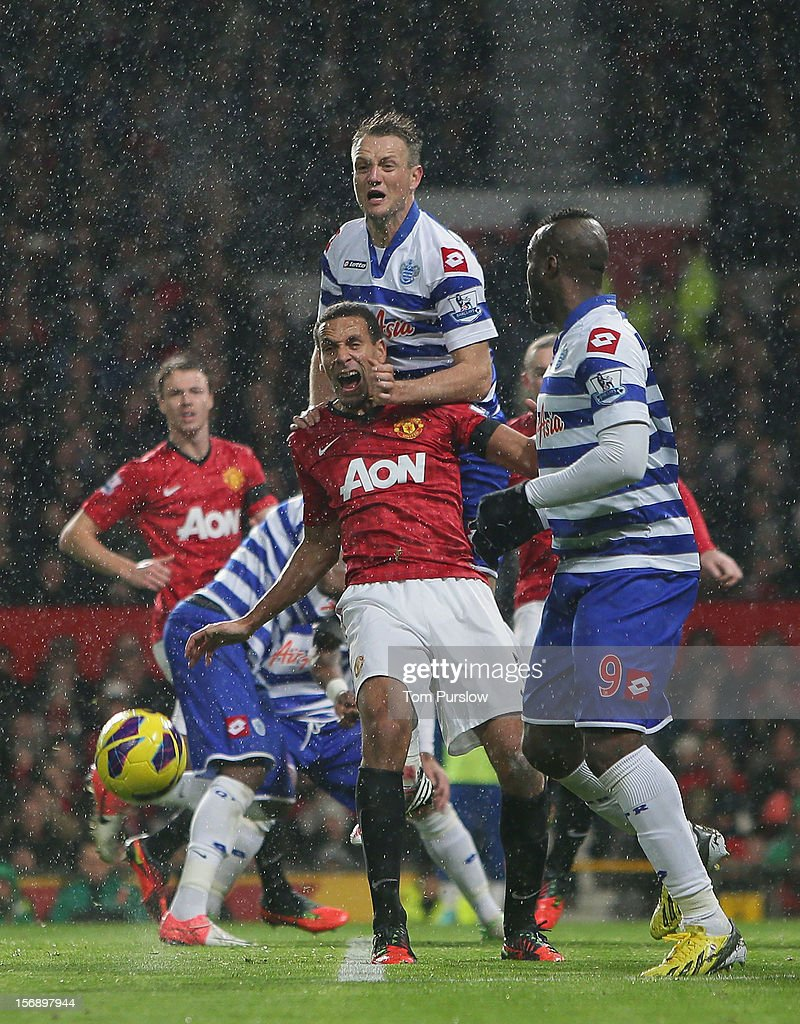 Rio Ferdinand of Manchester United in action with Clint Hill of Queens Park Rangers during the Barclays Premier League match between Manchester United and Queens Park Rangers at Old Trafford on November 24, 2012 in Manchester, England.