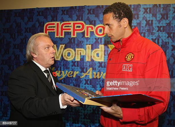 Rio Ferdinand of Manchester United is presented with his FIFPRO World XI award by Gordon Taylor of the PFA at Carrington Training Ground on October...
