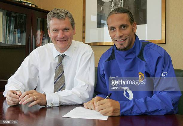 Rio Ferdinand of Manchester United poses with Chief Executive David Gill after signing a contract extension at Old Trafford on August 12, 2005 in...