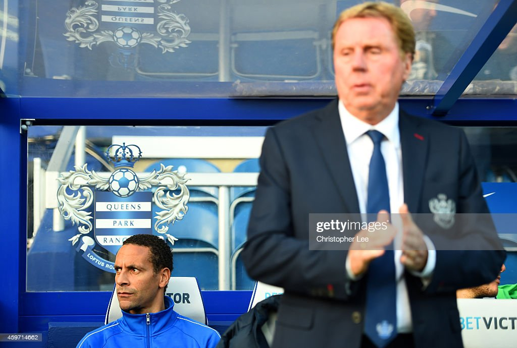 Rio Ferdinand of QPR looks on from the bench next to Harry Redknapp the QPR manager during the Barclays Premier League match between Queens Park Rangers and Leicester City at Loftus Road on November 29, 2014 in London, England.