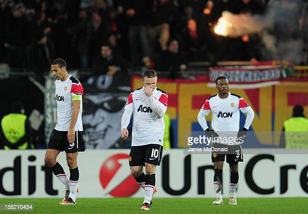 Rio Ferdinand Wayne Rooney and Patrice Evra of Manchester United walks dejected after Basel scored their second goal during the UEFA Champions League...