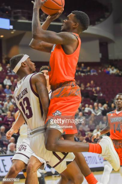 Rio Grande Valley Vaqueros guard Greg Bowie drives to the basket and rides up the body of Texas AM Aggie guard Duane Wilson during the basketball...