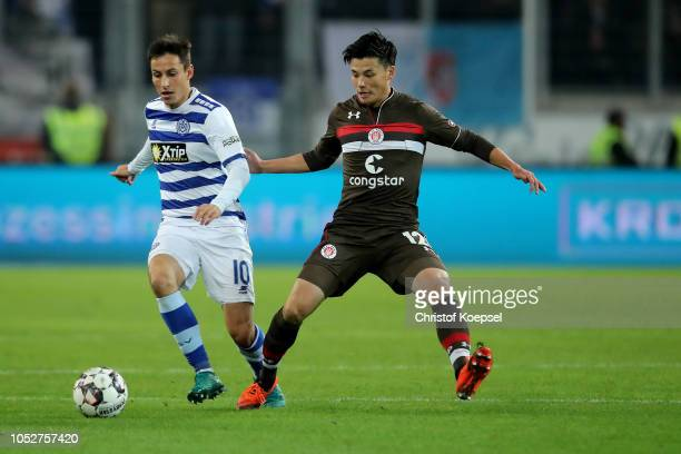 Rio Miyaichi of St Pauli challenges for the ball with Fabian Schnellhardt of Duisburg during the Second Bundesliga match between MSV Duisburg and FC...