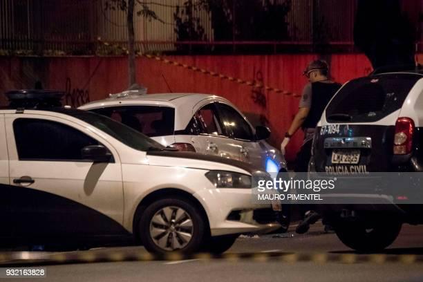 Rio's Civil Police officers investigate at Brazilian politician Marielle Franco's car where she was found shot dead in Rio de Janeiro Brazil on March...