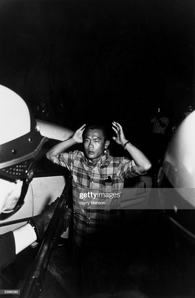 Riot equipped policemen apprehend a man for his ethnic origins, during race riots in the predominantly black area of Watts, Los Angeles, 11th-15th August 1965.