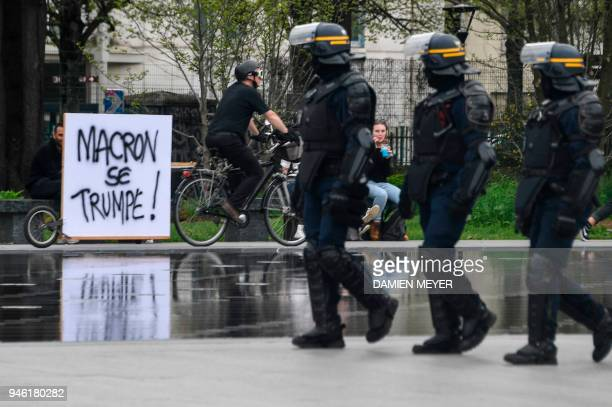 TOPSHOT Riot forces walk past a sign reading Macron is mistaken during a joint demonstration of French SNCF railway workers and students in Nantes...
