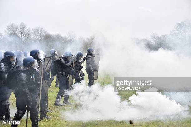 Riot gendarmes stand amid smoke on April 10, 2018 on the second day of a police operation to raze the decade-old camp known as ZAD at...