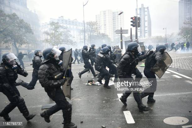 """Riot mobile gendarmes run on place d'Italie in Paris on November 16 during a demonstration of the """"yellow vest"""" marking the first anniversary of the..."""
