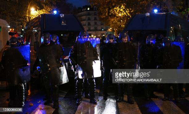 Riot mobile gendarmes stand side-by-side on Place de la Republique during a demonstration in Paris on december 12 against the 'global security' draft...
