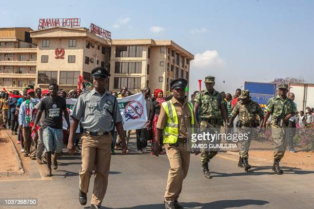 Riot police accompany protesters during nationwide antigovernment protests in Lilongwe on September 21 2018 Several hundred antigraft activists took...