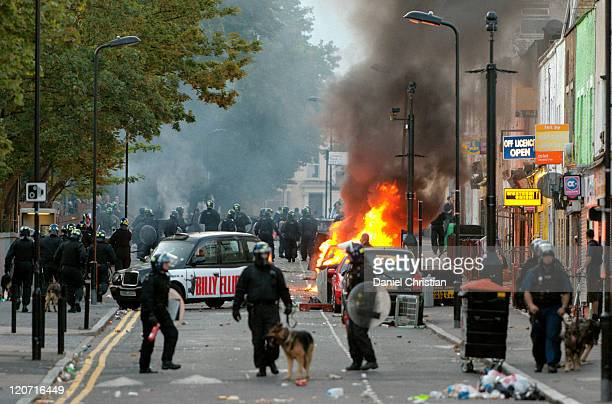 Riot police advance up Clarence Road as a car burns during clashes with rioters and looters in Hackney on August 8 2011 in London England Pockets of...