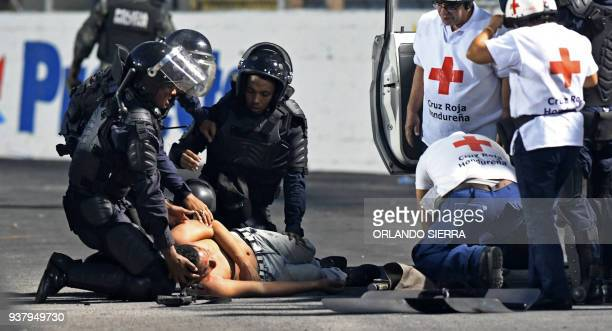 TOPSHOT Riot Police agents and Red Cross members help a football team supporter during the football match between Motagua and Olimpia at Tiburcio...