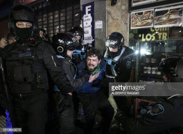 Riot police agents arrest a demonstrator outside the National Congress in Buenos Aires on August 9 after senators rejected the bill to legalize...