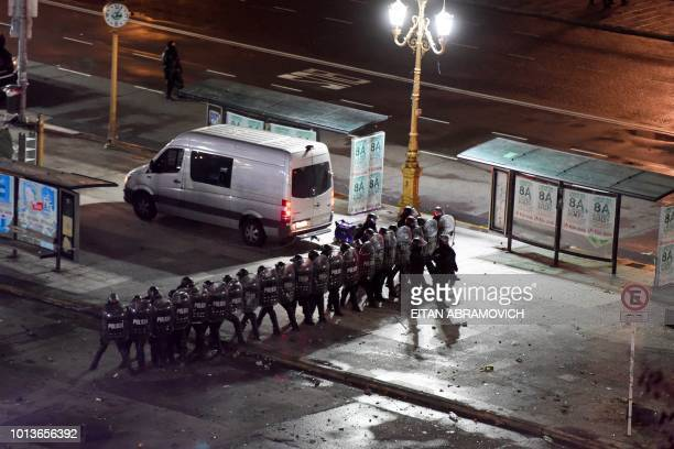 Riot police agents clash with demonstrators outside the National Congress in Buenos Aires on August 9 after senators rejected the bill to legalize...