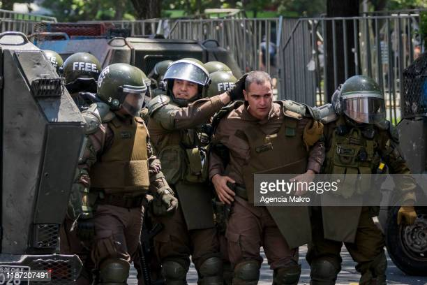 Riot police aid an officer who received a stone blow on the head during a national strike and general demonstration called by different workers...