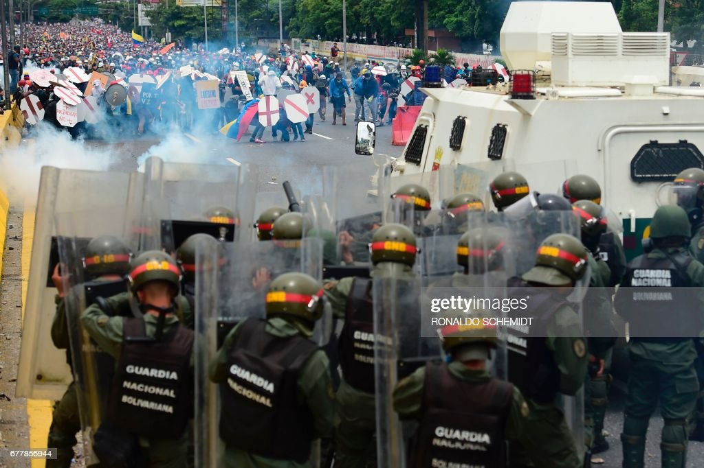 TOPSHOT - Riot police and demonstrators clash during a protest against Venezuelan President Nicolas Maduro, in Caracas on May 3, 2017. Venezuela's angry opposition rallied Wednesday vowing huge street protests against President Nicolas Maduro's plan to rewrite the constitution and accusing him of dodging elections to cling to power despite deadly unrest. /