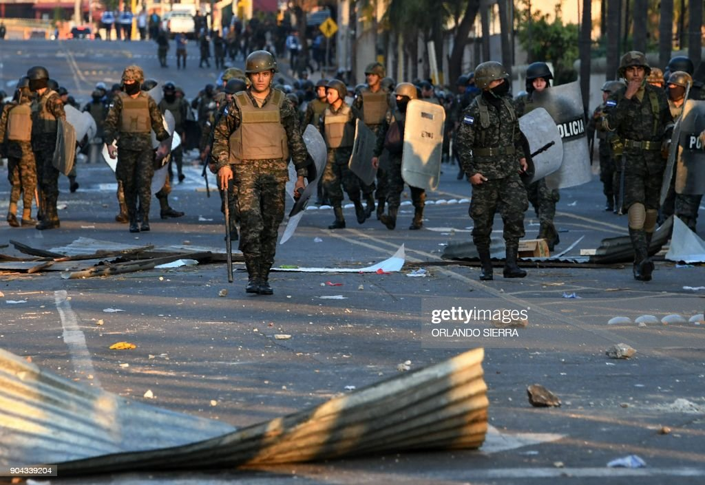Riot police and soldiers clash with supporters of the presidential candidate for the Honduran Opposition Alliance Against the Dictatorship, Salvador Nasralla, protesting near the presidential palace in Tegucigalpa on January 12, 2018. Thousands of people protested Friday in the Honduran capital against the reelection of President Juan Orlando Hernandez, as the January 27 start of his second term approaches. /