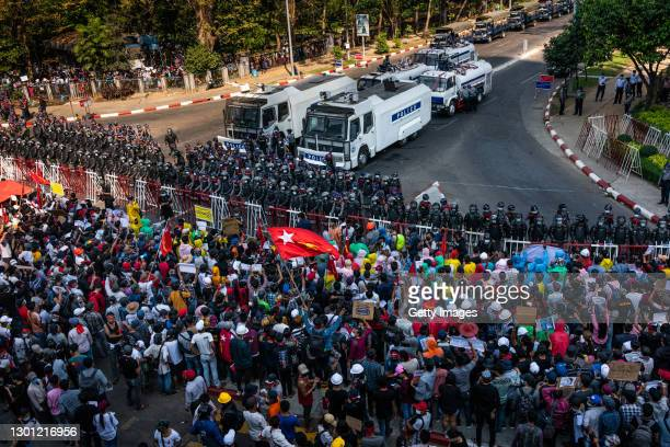 Riot police and water canon vehicles stand at a barricade as protesters approach them on February 09, 2021 in Yangon, Myanmar. Myanmar declared...