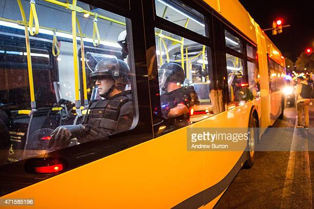 Riot police are brought in on a public bus to monitor protesters near a CVS pharmacy that was looted and burned by rioters on Monday after the...