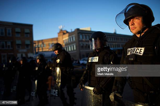 Riot police are illuminated by late afternoon light as they line the street to form a blockade after citywide riots over the death of Freddie Gray on...