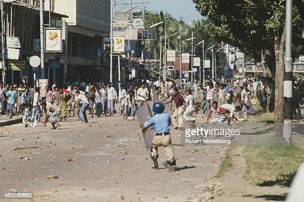 Riot police are pelted with stones during an antigovernment general strike in Dhaka Bangladesh circa 1989