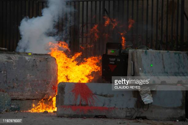 Riot police are reached by a petrol bomb during a protest against President Sebastian Pinera's government in Santiago January 10 2020 Chile has been...