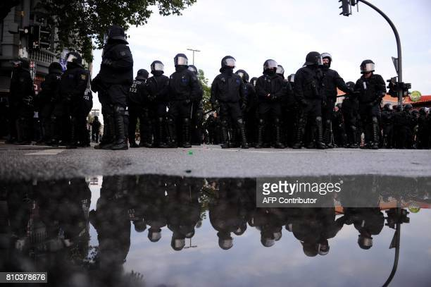 Riot police are reflected in water on July 7 2017 in Hamburg northern Germany where leaders of the world's top economies gather for a G20 summit...