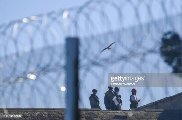Riot police are seen on the roof of a building during an incident at the YOI prison on August 20, 2020 in Portland, England.