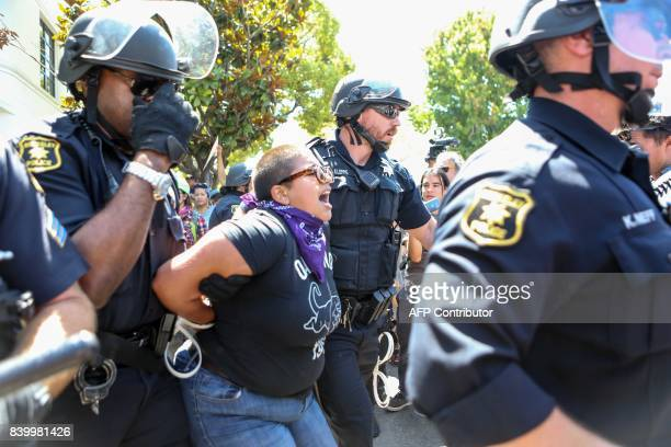 Riot police arrest a counter protester during the rightwing No To Marxism rally on August 27 2017 at Martin Luther King Jr Park in Berkeley...