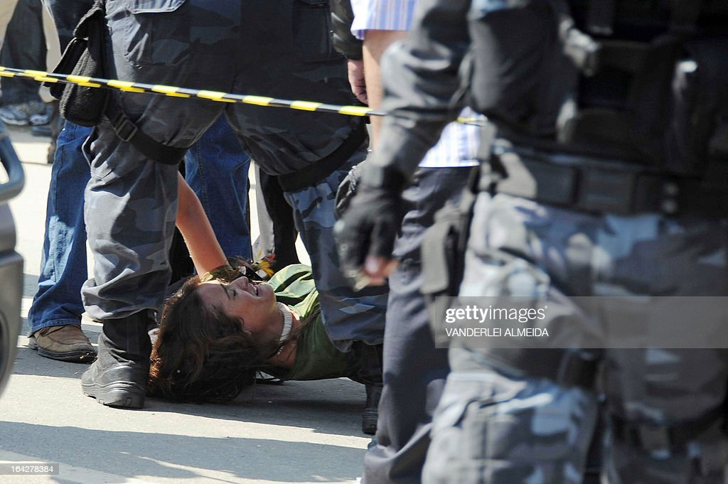 Riot police arrest a demonstrator at the former Indigenous Museum --aka Aldea Maracana-- next to the Maracana stadium in Rio de Janeiro, Brazil on March 22, 2013. Indigenous people have been occupying the place since 2006, which is due to be pulled down to construct a parking lot for the upcoming Brazil 2014 FIFA World Cup.