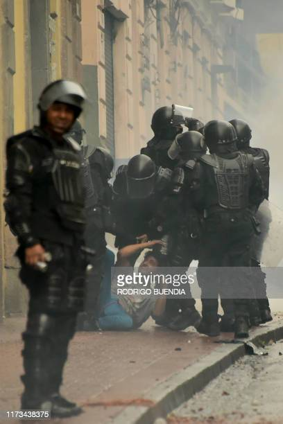 Riot police arrest a demonstrator during a protest following the announcement of a transport strike against Ecuadorean President Lenin Moreno's...
