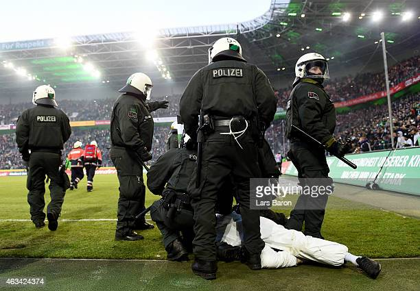 Riot police arrest a fan of Koeln after the Bundesliga match between Borussia Moenchengladbach and 1 FC Koeln at Borussia Park Stadium on February 14...