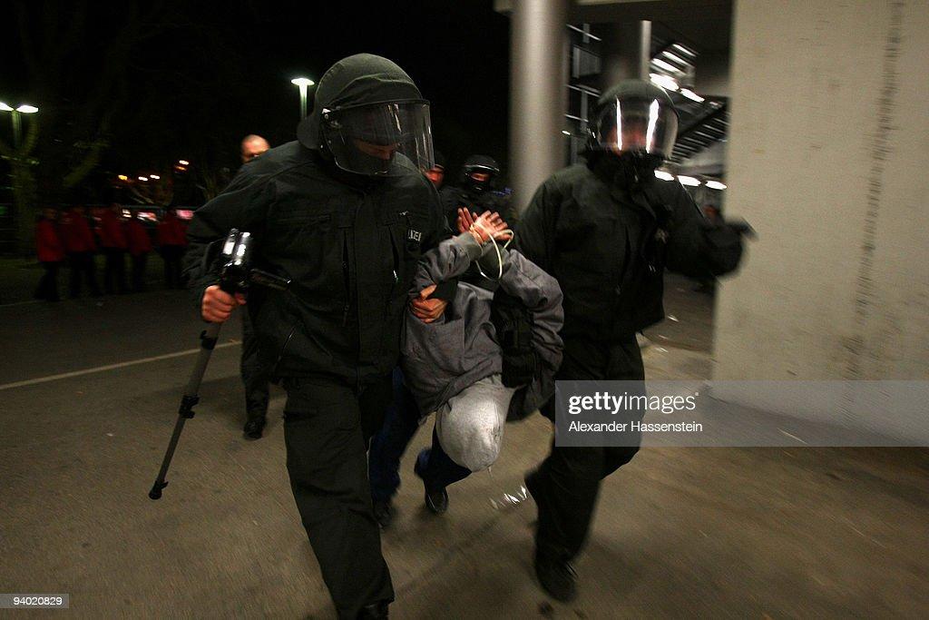 Riot police arrest a person after the Bundesliga match between VfB Stuttgart and VfL Bochum at Mercedes-Benz Arena on December 5, 2009 in Stuttgart, Germany.