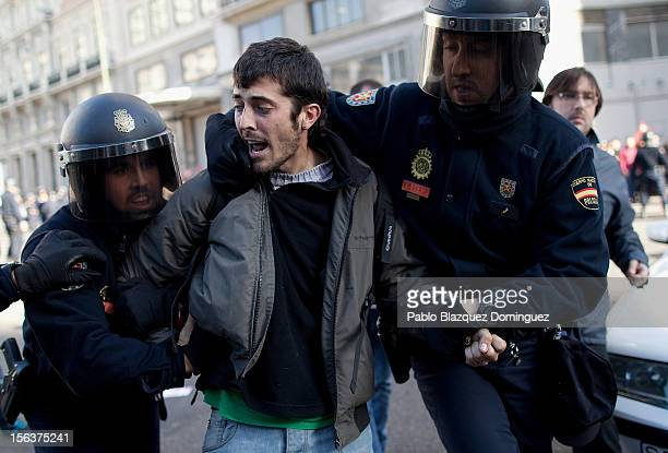 Riot police arrest a protester during a demonstration at Gran Via on November 14 2012 in Madrid Spain A coordinated general strike by unions in Spain...