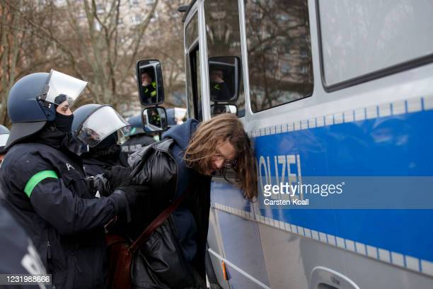 Riot police arrest a protester during an anti-lockdown protest march on the first anniversary of their Berlin demonstrations during the coronavirus...