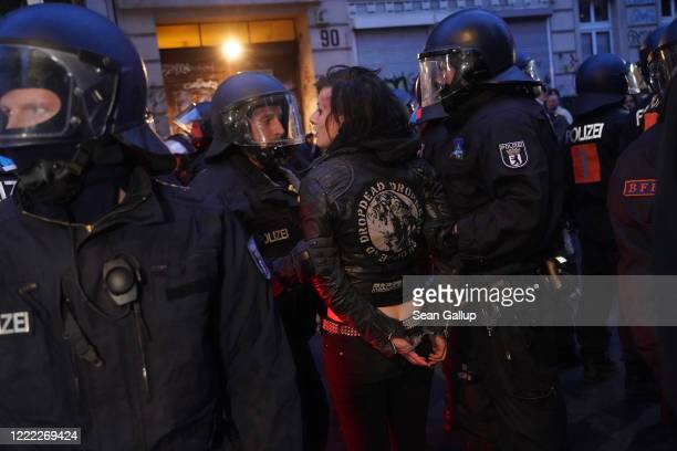 Riot police arrest a young woman during scattered leftwing protests in Kreuzberg district on May Day during the novel coronavirus crisis on May 1...