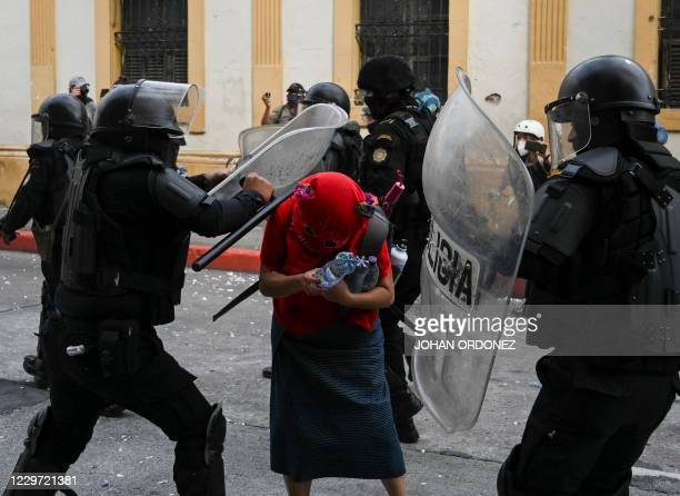 Riot police attack a demonstrator during a protest demanding the resignation of Guatemalan President Alejandro Giammattei, in Guatemala City on...