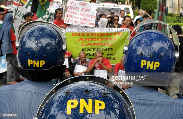 Riot police block a group of landless farmers as they protest outside the Malacanang palace in Manila on December 5 2008 callling for the...