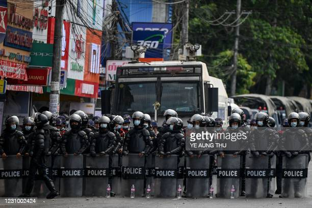 Riot police block a street as protesters gather for a demonstration against the military coup in Yangon on February 6, 2021.