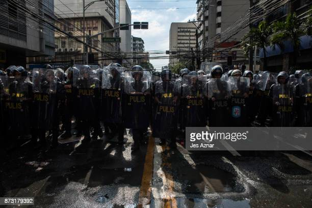 Riot police block a street leading to the US Embassy as protesters march in the streets of Manila on the day of US President Trump's arrival on...