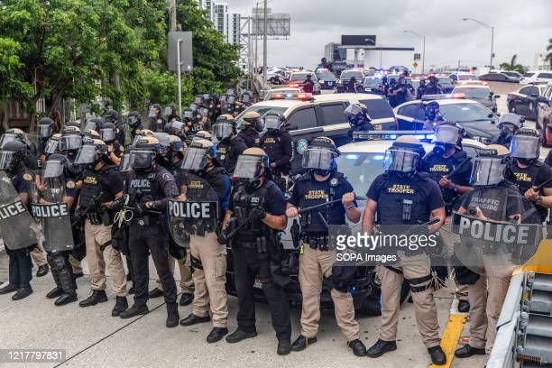 Riot police block access to I-195 in Miami from protesters demonstrating against police brutality. Protests have erupted in Miami and around the...