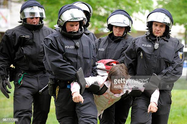 Riot police carry a left-wing participant of a sit-in, protesting against a planned neo-nazi demonstration, as they clear the streets in Berlin's...