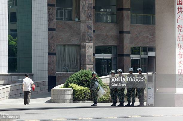 Riot police carrying batons and shields stand guard near the municipal government offices in Qidong, Jiangsu Province, China on 31 July 2012....