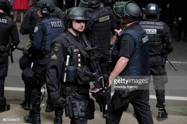 Riot police carrying crowd control weapons separate antifascist counter-protesters from far-right Patriot Prayer supporters during a freedom march...