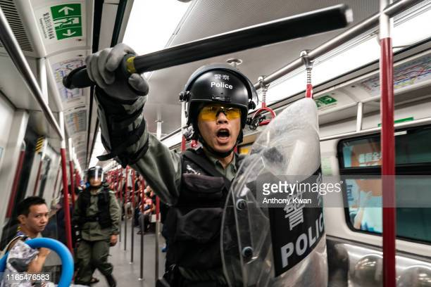 Riot police charge in a train at the Tung Chung MTR station after protesters block the transport routes to the Hong Kong International Airport on...