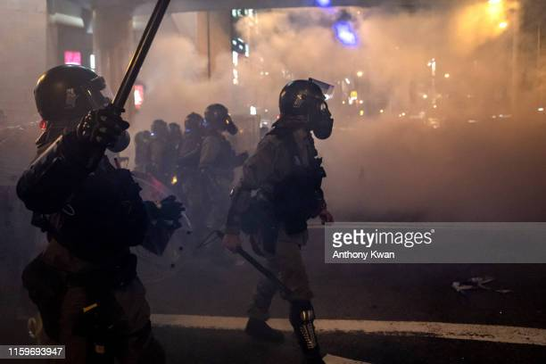 Riot police charge toward protesters in a fume of tear gas on an express way at Causeway Bay district on August 4, 2019 in Hong Kong, China....