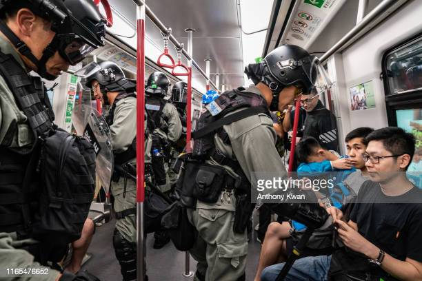 Riot police check passengers ID cards as they charge in a train at the Tung Chung MTR station after protesters block the transport routes to the Hong...